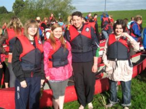 Young people wearing safety clothing gather outdoors